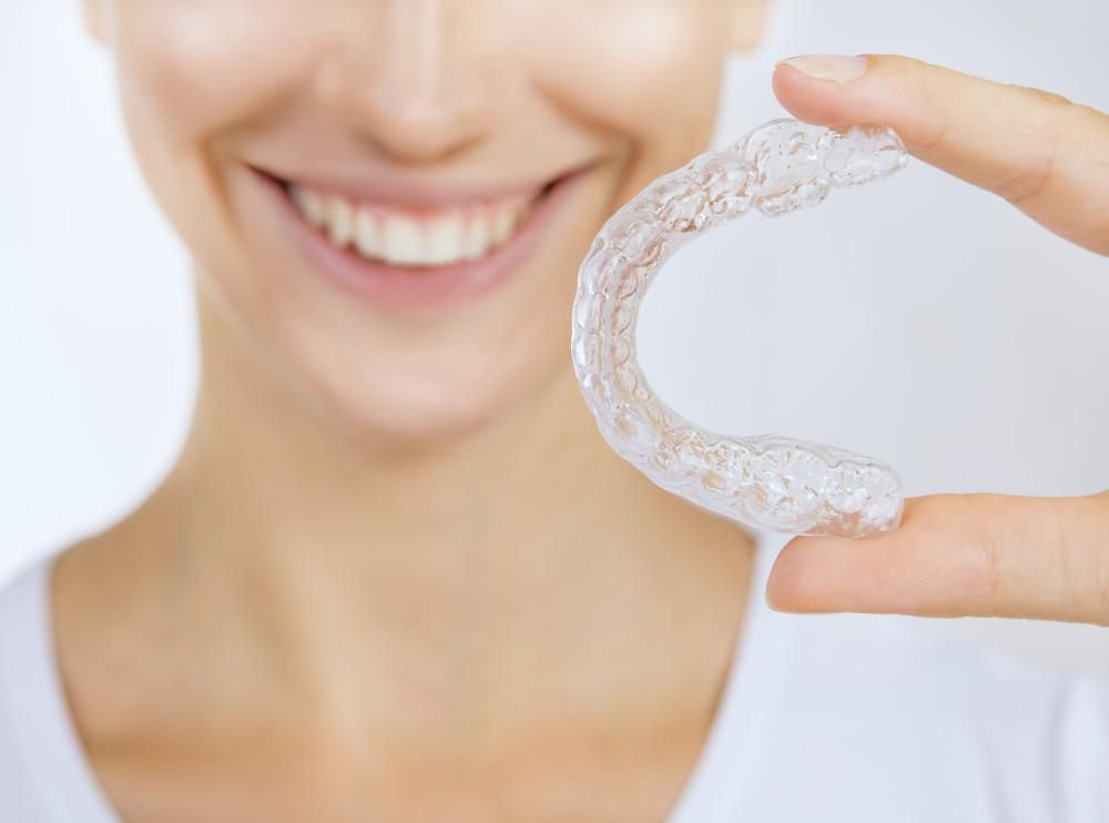 closeup image woman holding clear aligners