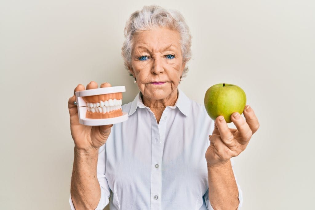 senior woman holding dentures in one hand and an apple in the other