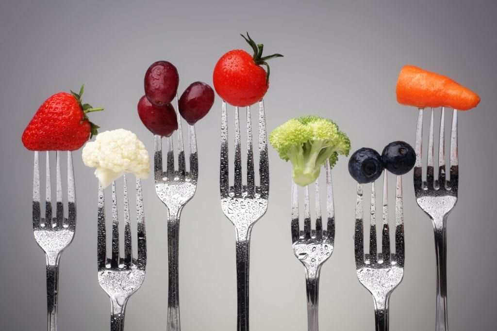forks holding different crunchy fruits and vegetables