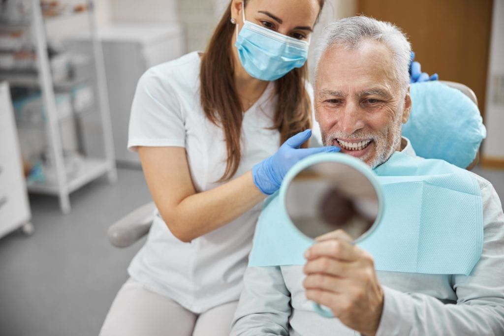 man sitting in dental chair smiling and looking in the mirror