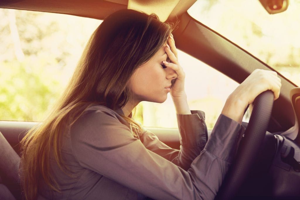 woman looking exhausted sitting in traffic